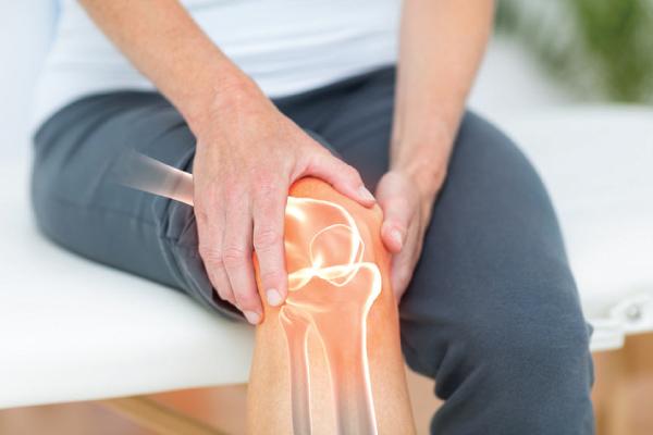 Pessoa com a mão no joelho e raio-x do joelho