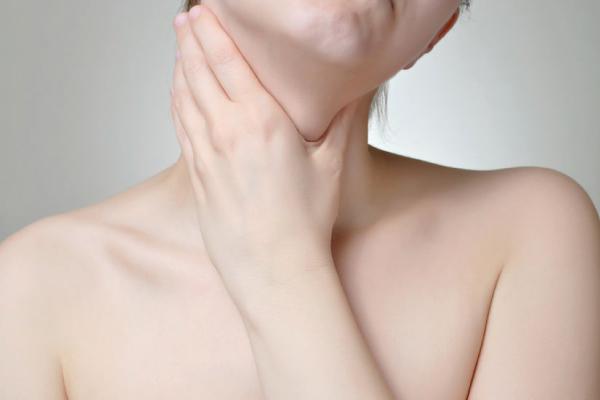 Mulher com tireóide colocando a mão no pescoço